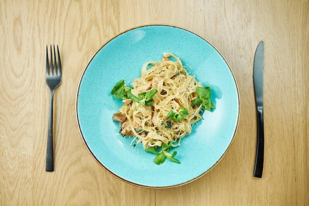 チキン、ホワイトソース、パルメザンチーズのタリアテッレ、木製のテーブルの青いボウル。伝統的な自家製イタリアンパスタ。閉じる