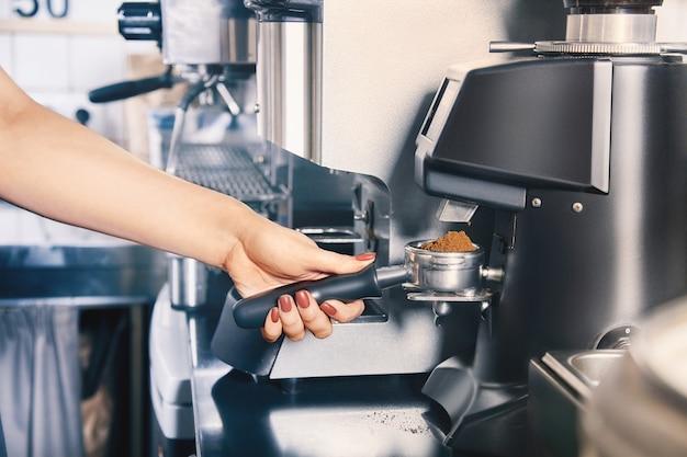 バリスタはコーヒーマシンを使用してコーヒー豆を粉砕します。コーヒーショップとバリスタのコンセプトです。焙煎したての豆を挽くコーヒーグラインダー。バリスタハンドホールド研削