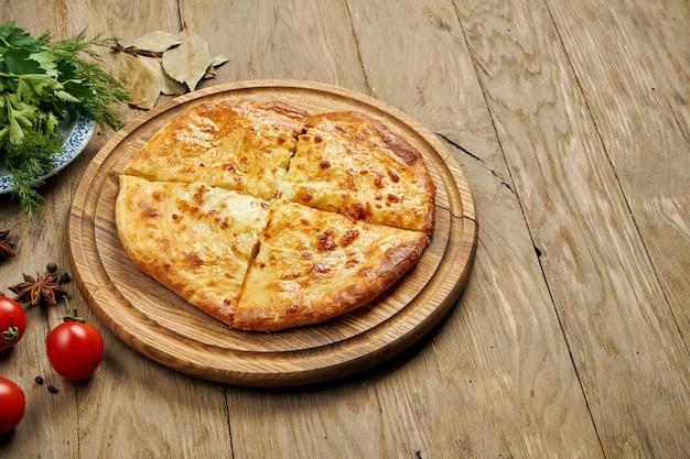 Крупным планом вид на вкусный традиционный хачапури - закрытый запеченный пирог, фаршированный плавленым сыром (сулугуни) или мясом на деревянный поднос. традиционная грузинская еда
