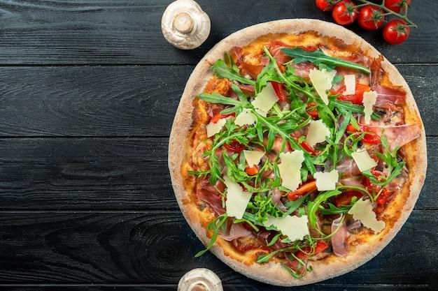 コピースペース付きの黒い木製のハモン、ルッコラ、パルメザンチーズ、チェリートマトと自家製の新鮮なピザ。上から見た食べ物の写真。フラット横たわっていた。イタリア料理。