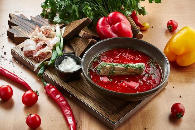 サワークリームと玉ねぎ、木製のまな板にベーコンと自家製のおいしいウクライナボルシチ。ウクライナ料理。宇宙食写真をコピーします。赤いスープ