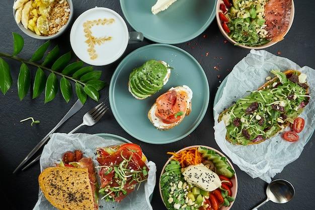 Ассорти хипстерской уличной еды на темной поверхности: тосты из авокадо с лососем и яйцом-пашот, кофе, миска будды и бутерброд с ветчиной