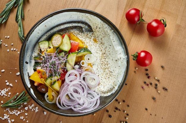 Классический греческий салат с помидорами, луком, огурцом, сыром фета и маслинами с оливковым маслом на белой тарелке на деревянной поверхности