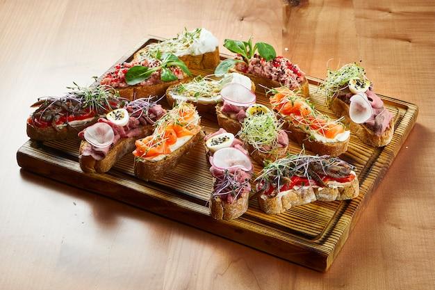 木製の表面にサーモン、牛肉、トマトの盛り合わせおいしいブルスケッタのビューをクローズアップ
