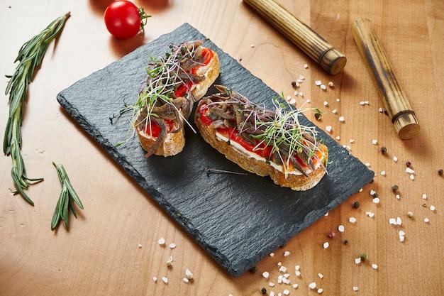 クローズアップビューの木製の表面に牛肉とトマトのおいしいブルスケッタ