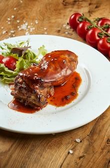 木製の表面の白いプレートにサラダと甘酸っぱいソースのローストバーベキューリブのビューをクローズアップ