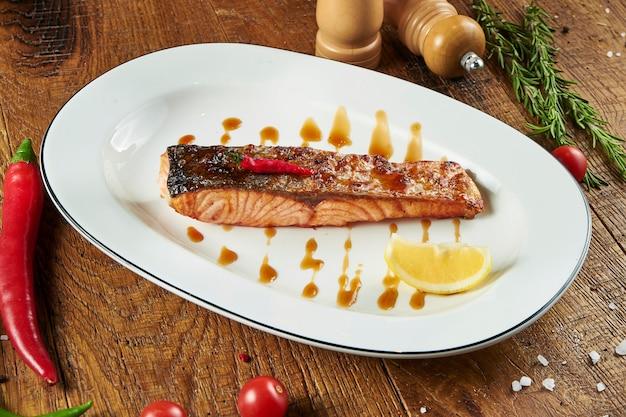 Вкусный стейк из лосося с чили-медовым соусом и лемонгарнисом на белой тарелке на деревянной поверхности