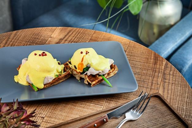 カフェで木製のテーブルの灰色の皿に伝統的なベルギーの朝食のビューをクローズアップ
