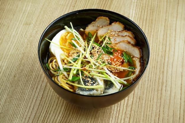Традиционный тайский рамен суп с лапшой, мясом, грибами шиитаке и яйцом в черной миске на деревянной поверхности