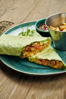 灰色の表面で分離された青いプレートの薄いピタパンで肉、サラダ、自家製ソースの食欲をそそるシャワルマロール。東洋料理。スライスしたケバブとグリルした肉。