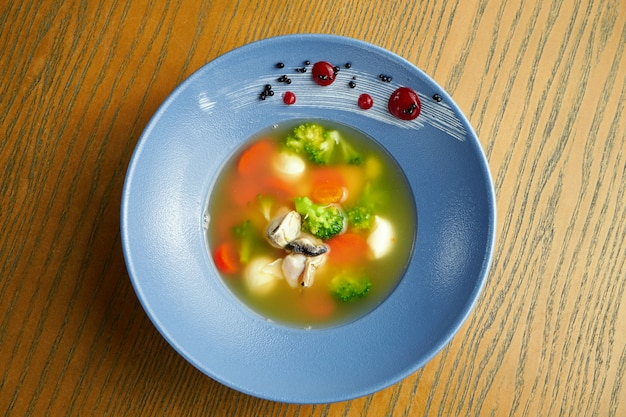 Аппетитный суп из морепродуктов. бульон с мидиями, морковью, брокколи и морскими гребешками в синей тарелке на деревянной поверхности