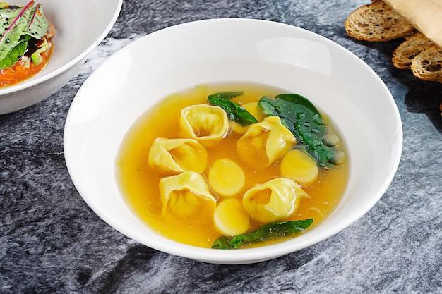 パスタとジャガイモと白いボウルビューチキンスープを閉じます。ヘルシーでバランスのとれたランチ。夕食のスープ。レシピ、メニューまたはポスターの写真。大理石のテーブル。フラットレイ
