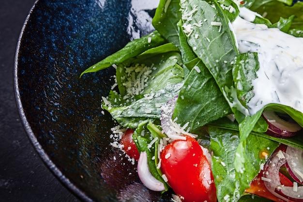 Салат с листьями салата, сметанным соусом, помидорами черри, красным луком и пармезаном