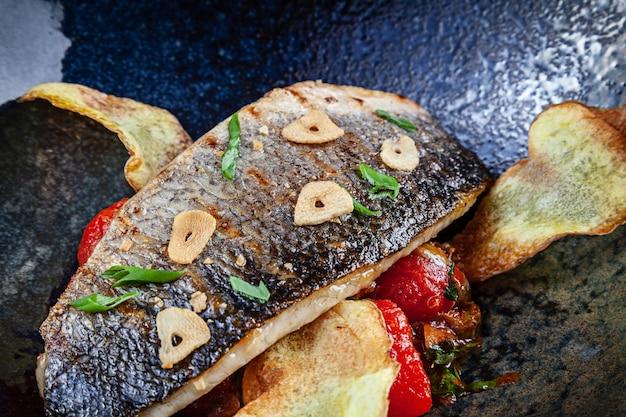 Крупным планом вид на свежий жареный сибас, подается с картофелем и помидорами черри в темной тарелке
