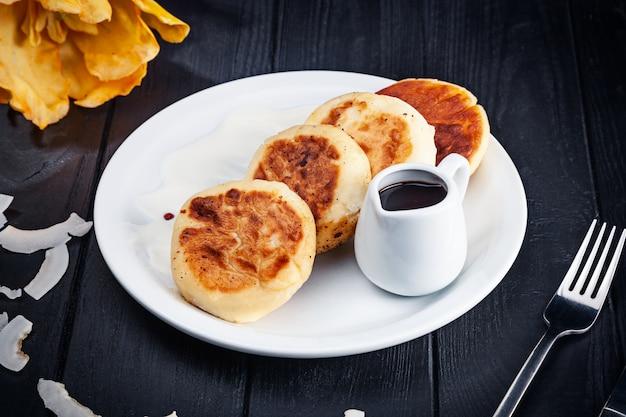 暗い木製の表面にホットチョコレートと白い皿にカッテージチーズのパンケーキを提供しています