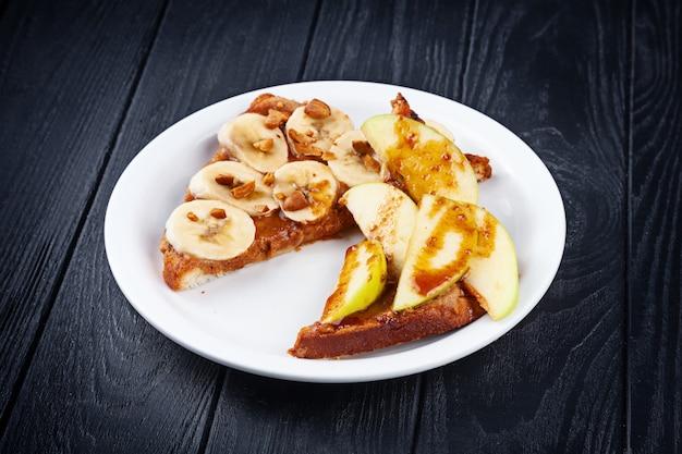Крупным планом вид на сладкий тост, подается на белой тарелке на темной деревянной поверхности