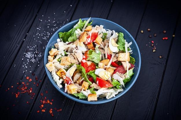 Вид сверху салат цезарь с курицей, листьями салата, сыром пармезан, помидорами
