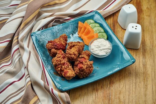 Пряные запеченные крылышки буйвола на синей тарелке
