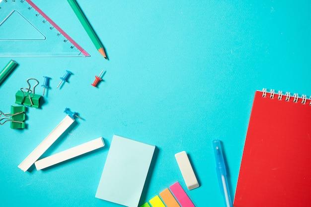 学校に戻るモックアップ。ノートブック、ステッカー、バインダー、ペン、チョーク、鉛筆でフラット横たわっていた構成。青色の背景に等尺性の概念。ポップアート。学用品。オーバーヘッド。ステーショナリーのモックアップのブランディング