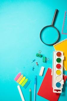 学校に戻るモックアップ。水彩、鉛筆、ノート、定規、消しゴムでフラットレイアウト構成。青色の背景に等尺性の概念。ポップアート。学用品。オーバーヘッド。ステーショナリーのモックアップのブランディング