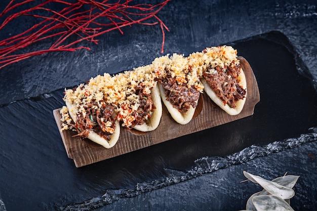 グアバオ、肉入りのまんじゅう(皮)のクローズアップ。バオは、暗い背景においしいトッピングを添えてください。アジア料理。アジアンサンドイッチ蒸しグアバオ。和風ファーストフード