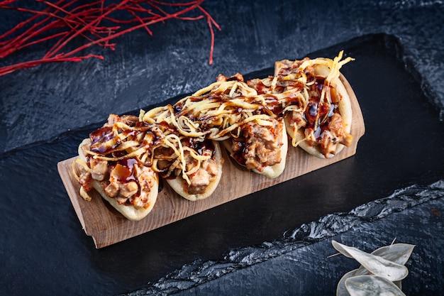 グアバオ、うなぎの蒸しパンにクローズアップ。バオは、暗い背景においしいトッピングを添えてください。アジア料理。アジアンサンドイッチ蒸しグアバオ。和風ファーストフード