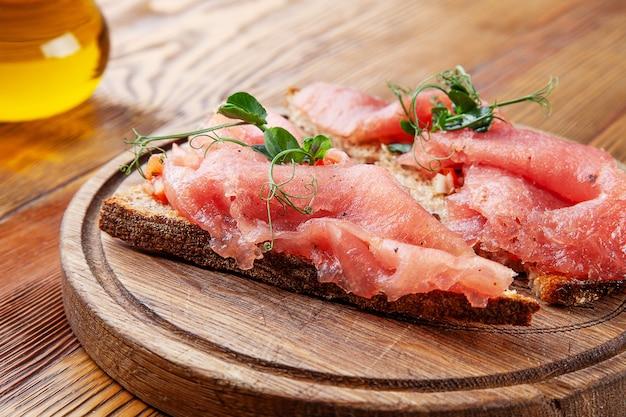マグロの美味しいブルスケッタ。セレクティブフォーカス。ブルスケッタと木製の背景にオリーブオイルのコンポジション。魚のパン。シーフード。メニューの食べ物の写真。自家製イタリア料理