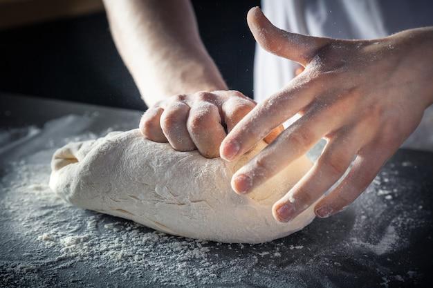 シェフは小麦粉で生地を準備します。生生地を手で練る横型。コピースペース。パスタ、ベーカリー、ピザ用のグルテンフリーの生地。ベイカーの職場。シェフが生地を作ります。料理、料理、ベーカリーのコンセプト