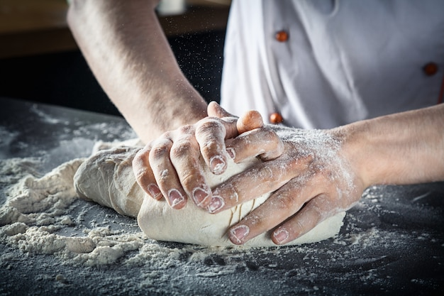 男性の手がピザ生地を準備します。キッチンのシェフがグルテンフリーのパスタやベーカリーの生地を準備します。パン屋はテーブルの上に生地をこねます。暗い背景。コピースペース。小麦パンをオーブンに