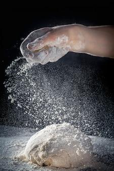 シェフは小麦粉で生地を準備します。暗い背景上のテーブルに生地の上に小麦粉を振りかける男性。垂直。コピースペース。飛行食のコンセプトです。パスタ、ベーカリー、ピザ用のグルテンフリーの生地