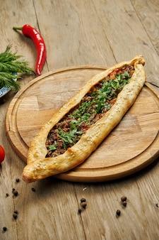 Пиде - турецкое блюдо в форме тортильи с говяжьим или мясным ягненком и зеленым луком на деревянном подносе. восточная пицца, рецепт или меню