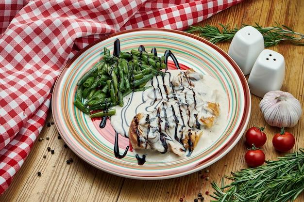 木の上のセラミックプレートにクリームソースとアスパラガスのおかずと鶏ササミのオーブン焼き。閉じる