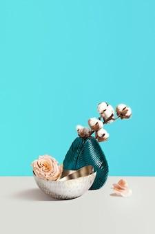 花瓶、花、装飾用のスペースを持つ青い背景の灰色のテーブルに装飾的な綿で創造的な構成。フラワーショップのコンセプトです。ミニマリズムの装飾