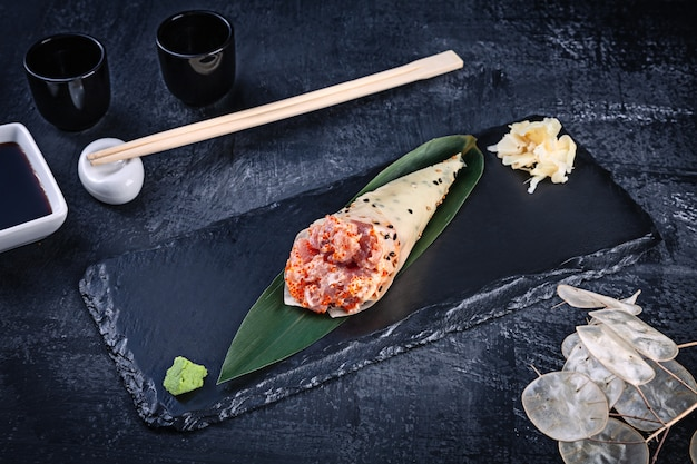 ツナとトビコキャビアを添えたまめのりのおいしい手巻き寿司のクローズアップ。醤油と生姜の暗い石のプレートで提供しています。コピースペース。手巻き、日本料理。健康食品