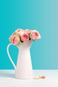 青い背景の上に白いセラミック花瓶スタンドで新鮮なバラ。花、テキスト用のコピースペース付きの花瓶とミニマリズムの組成物。フラワーショップのコンセプトです。グリーティングカード