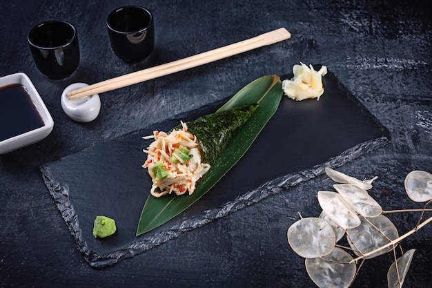 カニとトビコキャビア添えのおいしい手巻き寿司のクローズアップは、醤油と生姜の暗い石のプレートで提供しています。コピースペース。手巻き、日本料理。健康食品
