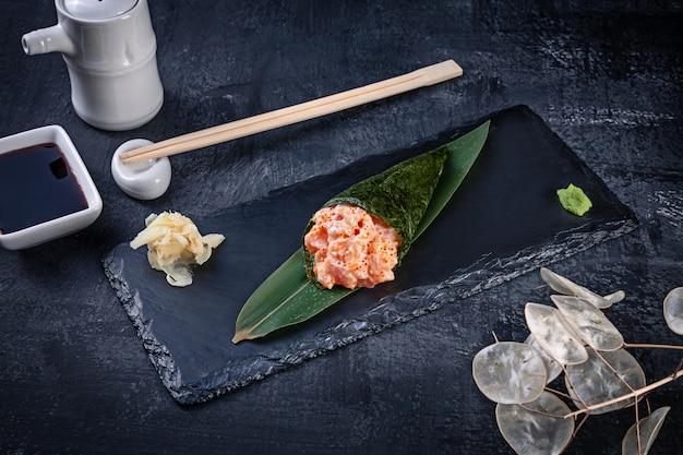 サーモンとトビコのキャビア添えのおいしい手巻き寿司のクローズアップは、醤油と生姜の暗い石のプレートで提供しています。コピースペース。手巻き、日本料理。健康食品