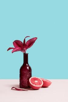ボトルの花瓶、赤い花とグレーのテーブルにグレープフルーツの創造的な静物画は青の背景に立っています。デザインのコピースペースと花屋のコンセプトイメージ。グリーティングカード。