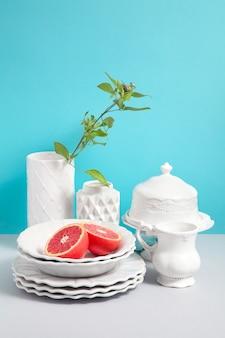 設計のためのスペースと青い背景に灰色のテーブルに白いスタイリッシュな陶器と花瓶の画像をモックアップします。セラミック食器のお店の画像。デザインの背景としてのキッチン静物