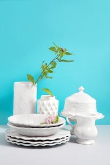 白い食器、食器、調理器具、デザインのためのスペースを持つ青い背景に灰色のテーブルの上に花瓶の花の画像をモックアップします。デザインの背景としてのキッチンの静物。コピースペース。