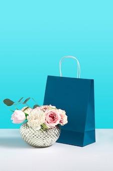 青い背景にペーパーギフトバッグスタンドの近くの花瓶にバラの花でイメージをモックアップします。デザインのためのスペースとギフトのコンセプトイメージ。花屋。ブランディングのモックアップ。販売または割引のコンセプト