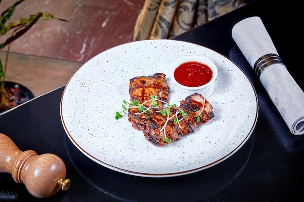 白い皿に赤いソースとグリルドチキンの部分のビューを閉じます。レストランの料理の背景。肉料理。デザインのスペースをコピーします。健康的なローストチキンフィレ。閉じる。横型