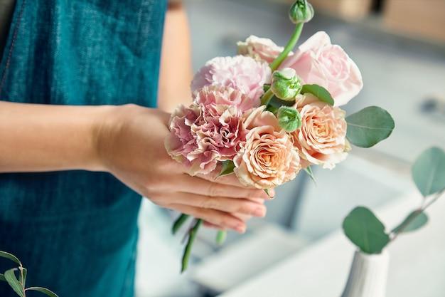 花のスタジオで花束を作る創造的な花屋のビューをトリミングしました。作業服の職場で若い女性。フラワーショップ、ビジネス、販売、フローリストリーのコンセプト。デザインのコピースペース