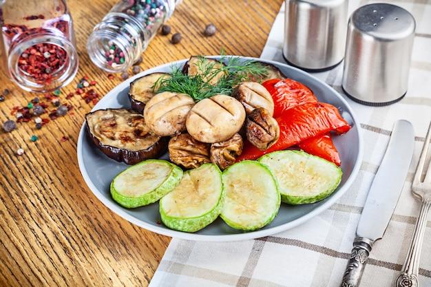 木製の背景に野菜のグリルのビューを閉じます。健康食品のバーベキュー。ビーガンミール。デザインのスペースをコピーします。おいしい焼き物盛り合わせ