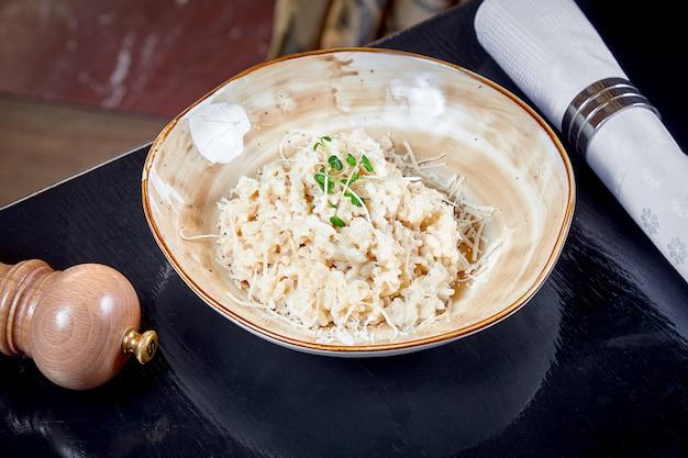 Закройте вверх по взгляду на ризотто с пармезаном сыра в шаре. обед еда. итальянская кухня. темный фон копировать пространство горизонтальная ресторанная еда.