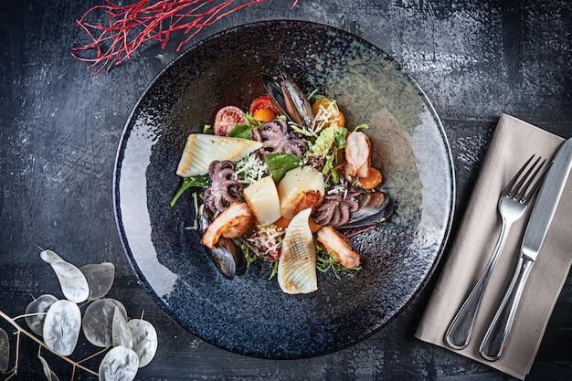 Вид сверху на салат из морепродуктов с кальмарами, креветками, морскими гребешками, мидиями, осьминогом, помидорами черри и зеленью. салатник подается на столик в ресторане. вид сверху еды. копировать пространство