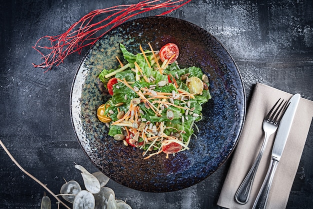 Свежий салат с листьями салата, сметанным соусом, помидорами черри, морковью. копировать пространство концепция здорового питания. обед или вкусная закуска. летнее меню. домашняя салатница. веганский, диетическое питание