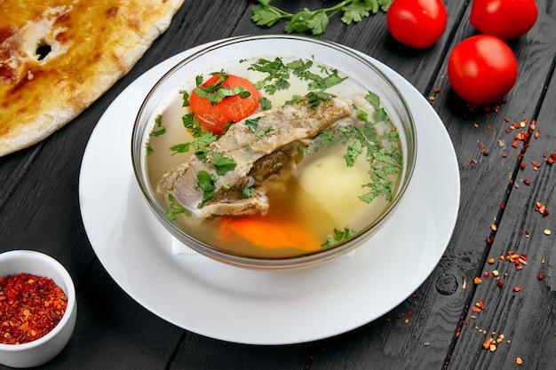 Суп шурпа в миску на фоне темных деревянных. грузинский густой суп с бараниной и специями. копировать пространство. грузинская кухня. еда на обед. вкусная суповая тарелка. концепция ресторана.
