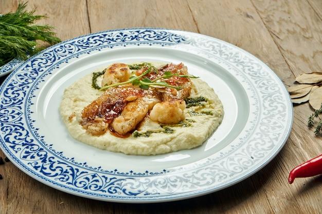Жареное филе судака с пюре из цветной капусты в белой тарелке на деревянной поверхности. вкусные морепродукты с гарниром