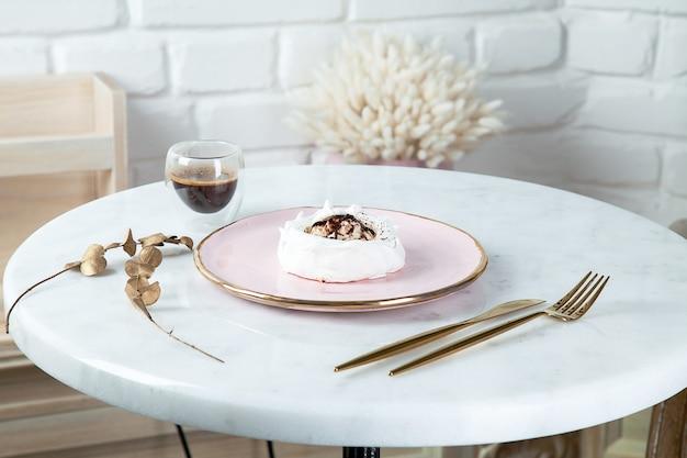 コーヒーと食品食器と白い大理石のテーブルに健康的なビーガンデザートアンナパブロワの平面図です。デザインのスペースをコピーします。新鮮なビーガン生デザート。健康食品。メレンゲの甘いケーキ